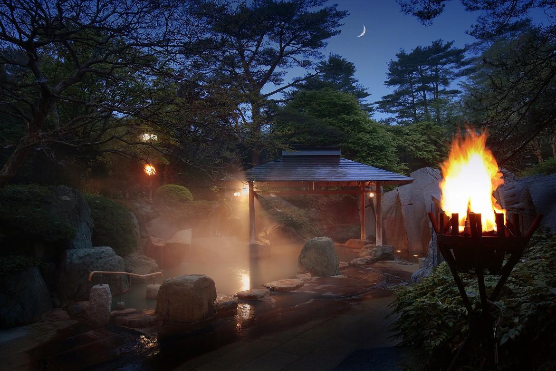 燃え盛る篝火とダイナミックな滝を眺め、名湯に浸る